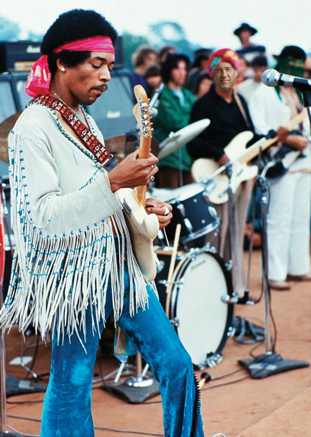 18 Aug 1969, Near Bethel, New York, USA --- Jimi Hendrix playing his guitar during his set at the Woodstock Music and Art Fair. Playing with Jimi Hendrix is Billy Cox (wearing a turban). --- Image by © Henry Diltz/CORBIS