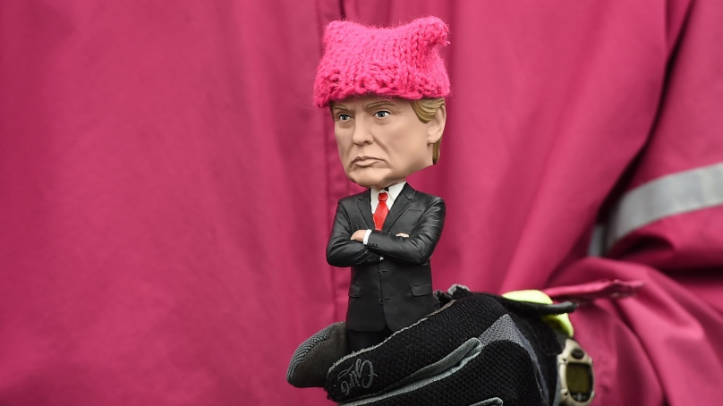 "A protester holds a Donald Trump bobble-head donned with a tiny pink ""pussy hat"" during Saturday's march in D"
